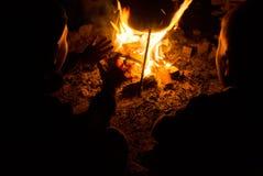 I bambini si siedono intorno al fuoco di accampamento alla notte Fotografie Stock Libere da Diritti