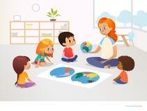 I bambini si siedono intorno alla mappa di mondo e l'insegnante femminile della testarossa li dimostra di modello di pianeta Terr illustrazione di stock
