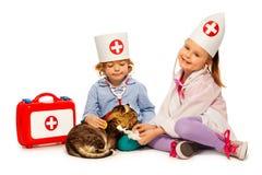 I bambini si sono vestiti alla zampa della fasciatura di bianchi ad un gatto Fotografia Stock
