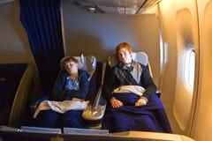 I bambini sono rilassantesi ed addormentati in un aereo in Cl di affari Immagine Stock