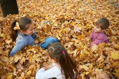 I bambini sono trovantesi e giocanti sulle foglie cadute nel parco della città di autunno immagini stock libere da diritti