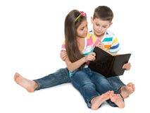 I bambini sorridenti hanno letto un vecchio libro Fotografia Stock