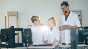 I bambini sorridenti stanno parlando con tecnico di laboratorio adulto stock footage