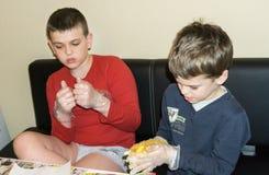 I bambini stanno colorando le uova di Pasqua Immagini Stock