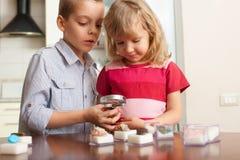 I bambini stanno considerando le pietre della lente d'ingrandimento Immagini Stock Libere da Diritti