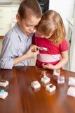 I bambini stanno considerando le pietre della lente d'ingrandimento Fotografie Stock