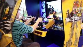 I bambini stanno giocando in trasformatori video Arcade Game di SEGA nel centro del gioco archivi video