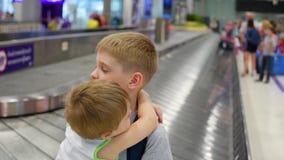 I bambini stanno nell'area di reclamo di bagaglio all'aeroporto video d archivio