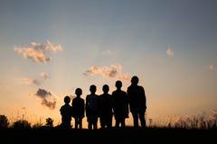 I bambini stanno stando sul campo con il fondo del tramonto Fotografie Stock