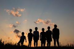 I bambini stanno stando sul campo con il fondo del tramonto Immagine Stock