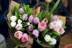 I bambini stanno tenendo due mazzi di tulipani Fotografia Stock