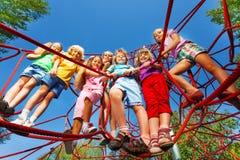I bambini stanno vicini sulle corde della rete del campo da giuoco Fotografie Stock Libere da Diritti