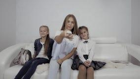 I bambini svegli che guardano la TV sul sofà a casa, bambine saltano sul sofà e prendono la TV a distanza archivi video