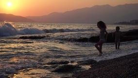 I bambini svegli e divertenti funziona sull'acqua, il ragazzo e la ragazza è sulla natura vicino ad un mare, ad un forte vento ed video d archivio