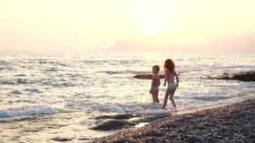 I bambini svegli e divertenti funziona sull'acqua, il ragazzo e la ragazza è sulla natura vicino ad un mare, ad un forte vento ed archivi video