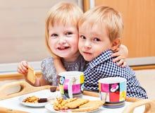 I bambini svegli stanno mangiando il dessert immagini stock libere da diritti