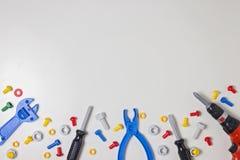 I bambini variopinti gioca i bulloni di plastica, i dadi, i cacciaviti, le pinze, il trapano e l'altra struttura degli strumenti  Immagini Stock Libere da Diritti