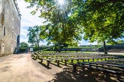 I banchi di legno a Kuressaare come il sole si stria attraverso gli alberi Fotografia Stock Libera da Diritti