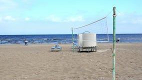 I banchi e la gente blu della rete di beach volley della spiaggia camminano archivi video