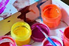I barattoli con i colori luminosi variopinti e una spazzola sono preparati per il lavoro del ` s dell'artista Fotografia Stock