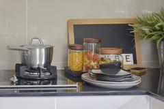 I barattoli del vaso e della pasta dell'acciaio inossidabile su granito nero completano contro Immagini Stock Libere da Diritti