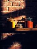 I barattoli di vetro brillanti hanno riempito di spezie variopinte assortite su uno scaffale di legno Immagine Stock