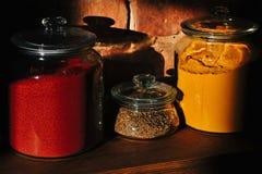 I barattoli di vetro hanno riempito di erbe e di spezie su uno scaffale di legno Fotografie Stock