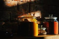 I barattoli di vetro hanno riempito di erbe e di spezie su uno scaffale di legno Fotografia Stock