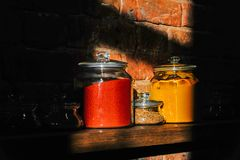 I barattoli di vetro hanno riempito di spezie su uno scaffale di legno Fotografia Stock