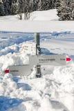 I bastoni del cartello della traccia di escursione da neve profonda nell'inverno delle montagne abbelliscono il giorno soleggiato Immagine Stock