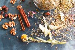 I bastoni di cannella, i dadi e una collezione dell'erba hanno sparso su un blu Immagini Stock