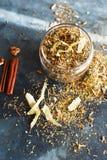 I bastoni di cannella, i dadi e una collezione dell'erba hanno sparso su un blu Fotografia Stock Libera da Diritti