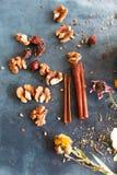 I bastoni di cannella, i dadi e una collezione dell'erba hanno sparso su un blu Immagini Stock Libere da Diritti