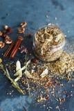 I bastoni di cannella, i dadi e una collezione dell'erba hanno sparso su un blu Fotografia Stock