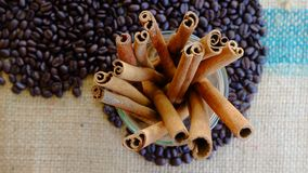 I bastoni di cannella in un vetro su un cuore modellano i chicchi di caffè Fotografia Stock