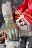 I bastoni di incenso ed i fiori secchi sono disposti sulla coscia di una statua di Buddha (Tailandia) Immagini Stock Libere da Diritti