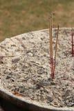 I bastoni di incenso sono stati messi in una ciotola nel cortile di un tempio buddista (Tailandia) Fotografie Stock Libere da Diritti