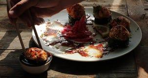 I bastoni per la gru a benna dei sushi hanno cotto i rotoli ed hanno immerso in salsa di soia archivi video