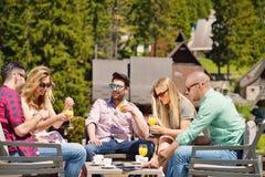 I bei amici alla moda stanno utilizzando una compressa digitale, caffè bevente e stanno sorridendo mentre riposavano nel parco Immagine Stock