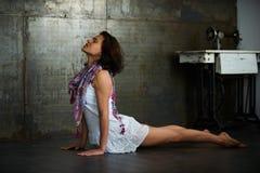 I bei 35 anni della donna pratica il asana Urdhva Mukha Svanasana - cane ascendente di yoga del rivestimento nella stanza d'annat Immagine Stock