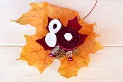 I bei fiori della fibula fatti da feltro, dalle perle e dalle foglie del metallo, giallo caduto va su un fondo di legno bianco Fotografia Stock