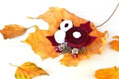 I bei fiori della fibula fatti da feltro, dalle perle e dalle foglie del metallo, giallo caduto va su un fondo di legno bianco Fotografia Stock Libera da Diritti