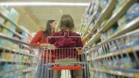 I bei giovani genitori e la loro piccola figlia sveglia stanno sorridendo mentre sceglievano l'alimento nel supermercato La ragaz stock footage