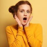 I bei giovani hanno sorpreso la donna del redhair sopra fondo giallo fotografia stock libera da diritti