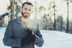 I bei giovani uomini barbuti che si rilassano sull'inverno camminano in foresta nevosa, bloccaggio schietto fotografia stock libera da diritti