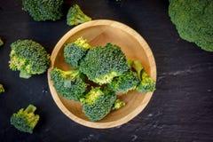 I bei ornamenti dei broccoli su un piatto di legno su un'ardesia imbarcano Fotografia Stock