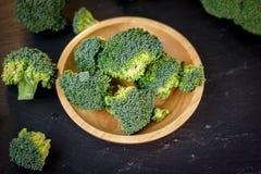 I bei ornamenti dei broccoli su un piatto di legno su un'ardesia imbarcano Fotografia Stock Libera da Diritti