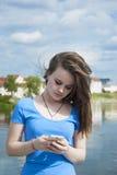 I bei supporti teenager della ragazza su un fondo della città con un telefono cellulare invia un messaggio Fotografia Stock