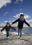 I believe I can fly. Girls have fun on a sea coast royalty free stock photo