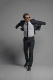 I believe I can fly. Full length of confident young businessmen. In sunglasses posing while on grey royalty free stock photo